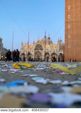 confetti and colored paper on the ground of deserted San Marco Square during the carnival and the crisis COVID-19, Basilica of Saint Mark on background