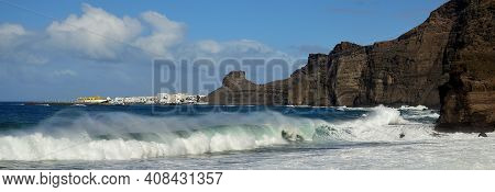Guayedra Beach With Big Wave Breaking And Port Of Las Nieves In The Background, Coast Of Agaete, Gra