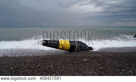 A Large Black And Yellow Buoy Washed Ashore After A Storm. A Broken Sea Buoy Lies On The Shore Again