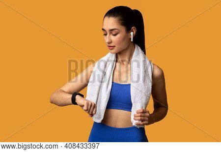 Workout And Electronics Concept. Portrait Of Fit Young Sportswoman Wearing Bracelet, Checking Fitnes