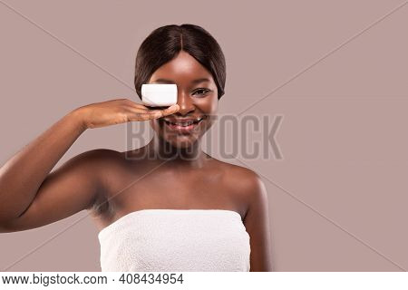 Skin Care. Beauty Portrait Of Happy Black Woman Holding White Jar With Moisturising Cream On Her Pal