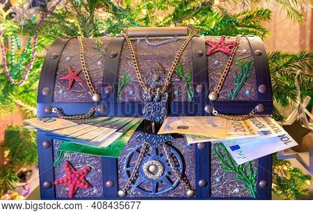 Gift Chest With Money On The Background Of The Christmas Tree. Wealth Concept For The Holiday. Safet
