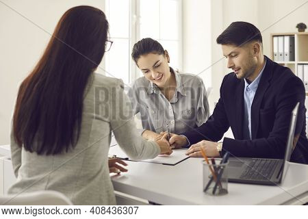 Happy Couple Meeting Realtor And Signing Lease, Mortgage Or House Purchase Agreement