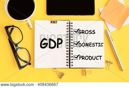 Gdp - Gross Domestic Product Text On Notepad And Office Accessories On Yellow Desk.