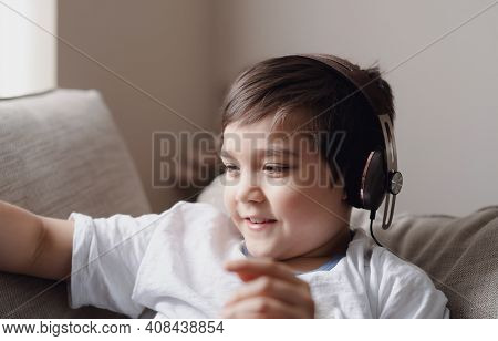 Close Up Happy Kid With Smiling Face,  Head Shot Positive Child Wearing Headphone Listening Music In