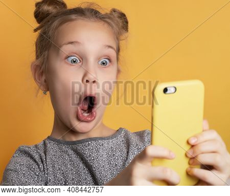 Close Up Of Surprised Little Girl With Wide Open Mouth Looking At Phone Holding In Hands. Portrait O