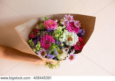 Hand With Beautiful Bouquet Of Seasonal Flowers On Pink Background. Pink Zinnia, White Dahlia, Cosmo