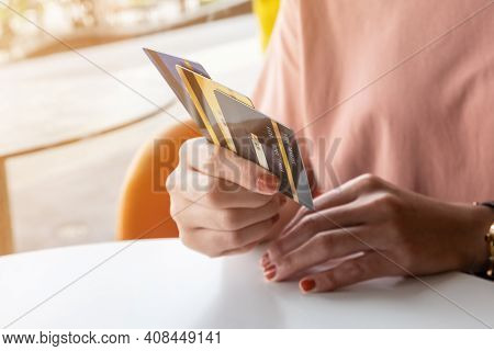 Cropped Shot View Of Female Hands Holding Her Credit Cards. Credit Card Lets Cardholders Borrow Fund