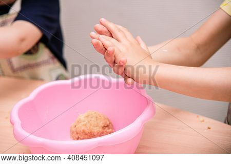 Girl Kid Sculpts From Dough, Creativity With Dough. Small Childrens Hands Close-up, Pink Bowl With D