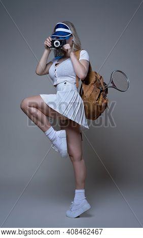 Sportswoman With Photocamera Shots And Poses In White Background. Portrait Of A Female Athlete Dress