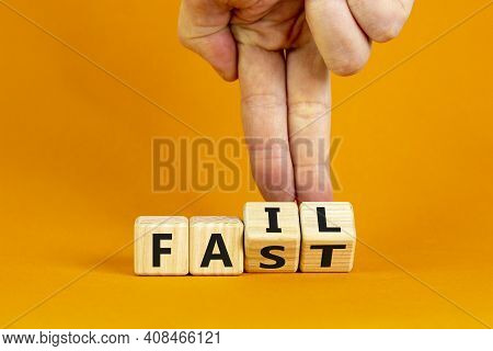 Fail Fast Symbol. Businessman Turns Wooden Cubes With Words 'fail Fast' On Beautiful Orange Backgrou