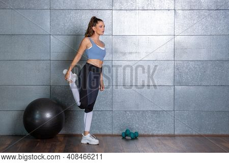 Woman In Sports Wear Warming Up Before Workout And Stretching Her Leg In Front Of Metal Background A