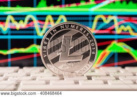 Close Up Photo Of Silver Shining Lite Coin Standing On White Button Of Keyboard With Multicolored Di