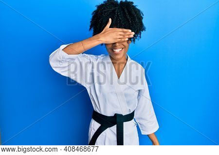 African american woman with afro hair wearing karate kimono and black belt smiling and laughing with hand on face covering eyes for surprise. blind concept.