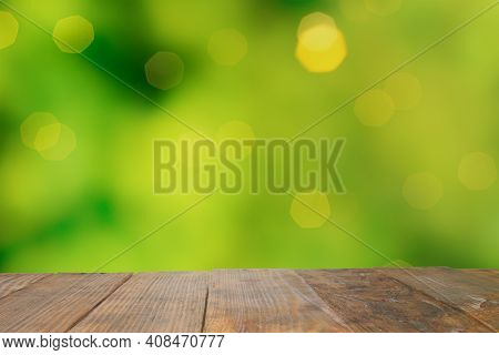 Empty Old Dark Wooden Rustic Table Top Made Of Planks With Uneven Edges On Blurred Garden And Green