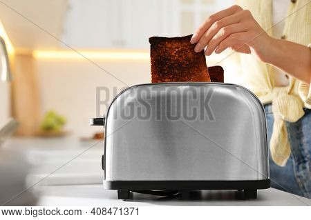Woman Taking Slice Of Burnt Bread From Toaster In Kitchen, Closeup