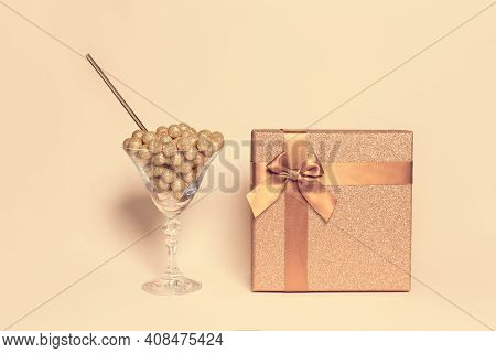 Creative Composition Made Of Present Box With Bow, Martini Glass With Decorative Golden Balls And St