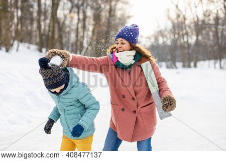 Mother and kid having snowball fight in winter park