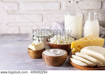 Various Fresh Dairy Products, Milk, Sour Cream, Cottage Cheese, Yogurt And Butter On A Light Stone C