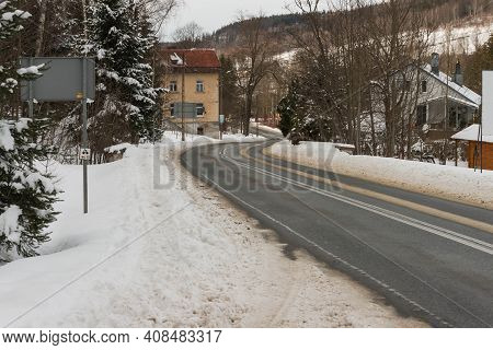 Asphalt Road In Winter, In The Jizera Mountains. Jizera Mountains In Poland. Asphalt Road Covered Wi