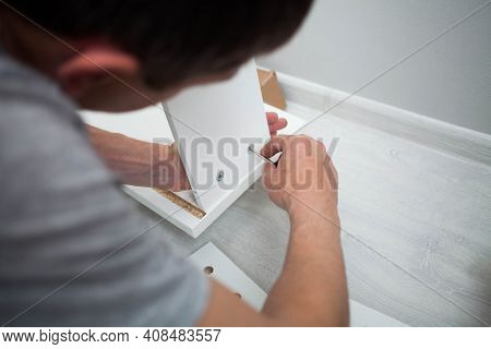 Close Up Of Man Hand, Furniture Assembler Make Flat  Pack White Furniture Assembly Service At Home.