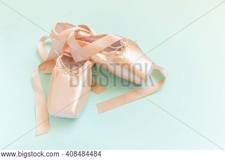 New Pastel Beige Ballet Shoes With Satin Ribbon Isolated On Blue Background. Ballerina Classical Poi
