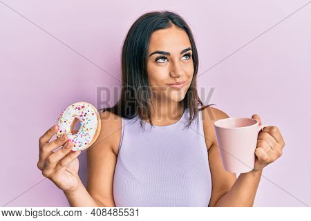 Young brunette woman eating doughnut and drinking coffee smiling looking to the side and staring away thinking.