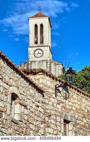 Stone Houses And Belfry With Clock In Village Of Balazuc In France