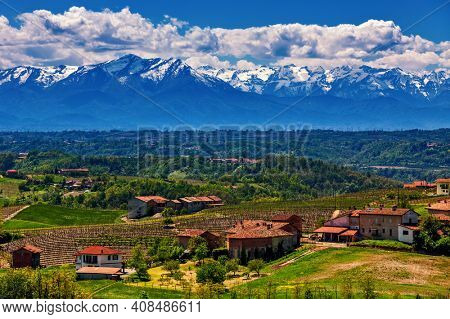 View of small village on green hills as snowy mountain ridge on background in Piedmont, Northern Italy.