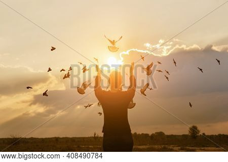 Doves Fly Towards The Sunlight While A Woman Prays.