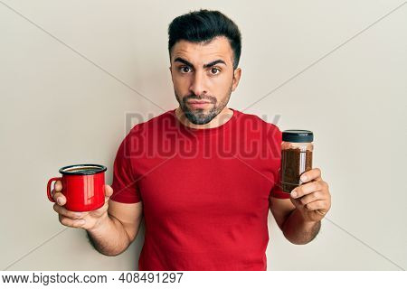 Young hispanic man holding cup of soluble coffee skeptic and nervous, frowning upset because of problem. negative person.