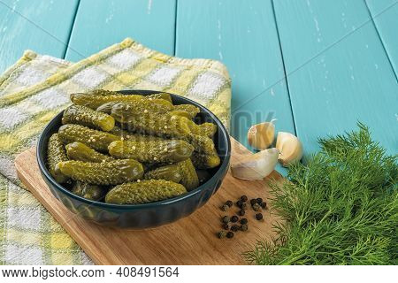 Delicious Pickled Cornichons In A Dark Ceramic Bowl, Garlic, Pepper And Dill Over Blue Wooden Table.