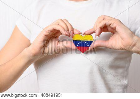 Love Venezuela. The Girl Holds A Heart In The Form Of The Flag Of Venezuela On Her Chest. Venezuelan