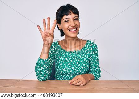 Beautiful brunettte woman wearing casual clothes sitting on the table showing and pointing up with fingers number four while smiling confident and happy.