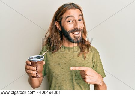 Attractive man with long hair and beard drinking mate infusion smiling happy pointing with hand and finger