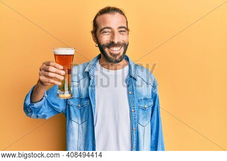 Attractive man with long hair and beard drinking a pint of beer looking positive and happy standing and smiling with a confident smile showing teeth
