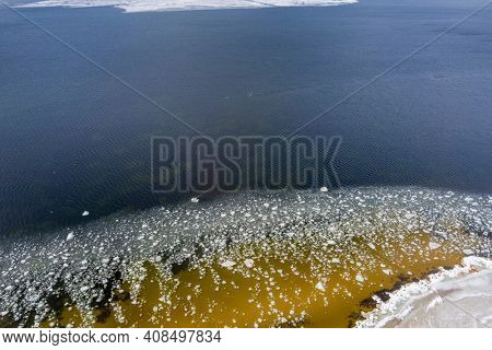 Ice blocks drifting around in a calm sea water creating interesting aerial patterns.