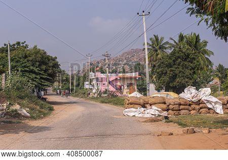 Sanapur, Karnataka, India - November 9, 2013: Main Road In Hamlet With Stack Of Brown Jute Bags Fill