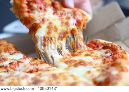Close-up Of Person Hand Taking Piece Of Pizza. Worker Having Lunch. Cheese Pizza With Sausage Slices