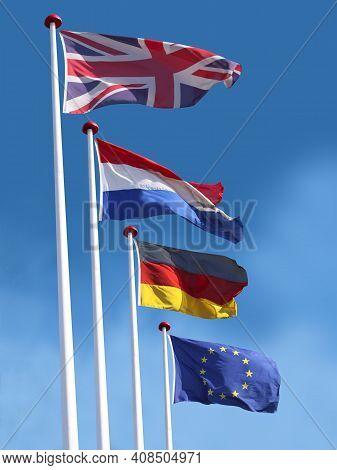 Flags Of United Kingdom, France, Germany And The European Union On Flagpoles. Flag Of United Kingdom