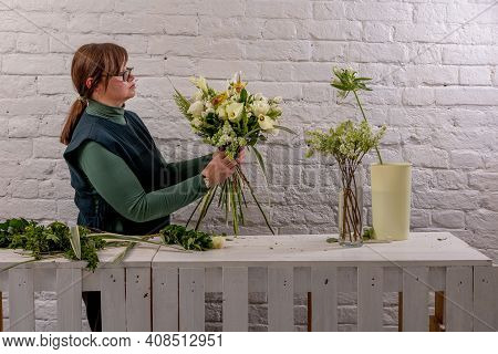 Florist Workplace On The Light Background. The Florist Creates A Floral Arrangement Of Roses, Lilacs