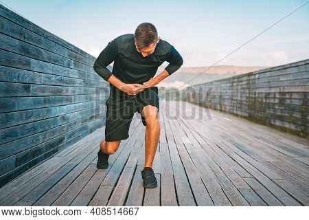 Man Runner Having Stomach Side Cramps Or Stitch During Training. Athlete Suffering From Pain In His