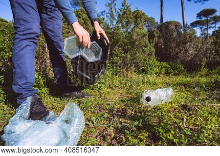 Man Cleaning-up The Forest Of Plastic Garbage. Nature Cleaning. Volunteer Picking Up A Plastic In Th