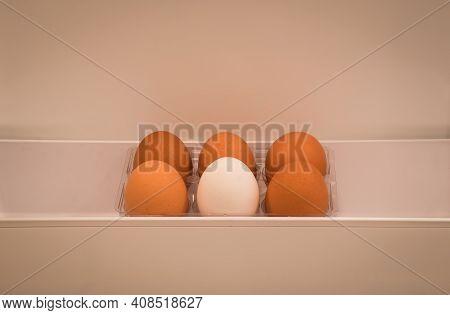 Half A Dozen Organic Eggs 1 White And 5 Brown Kept In A Fridge Door