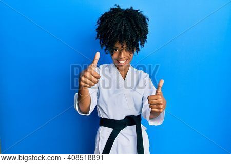 African american woman with afro hair wearing karate kimono and black belt approving doing positive gesture with hand, thumbs up smiling and happy for success. winner gesture.
