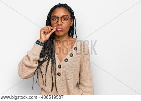 African american woman wearing casual clothes mouth and lips shut as zip with fingers. secret and silent, taboo talking