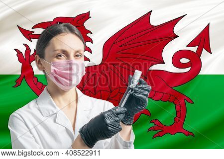 Girl Doctor Prepares Vaccination Against The Background Of The Wales Flag. Vaccination Concept Wales
