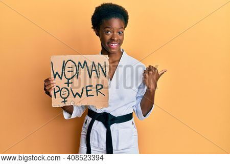Young african american girl wearing karate kimono holding woman power banner pointing thumb up to the side smiling happy with open mouth