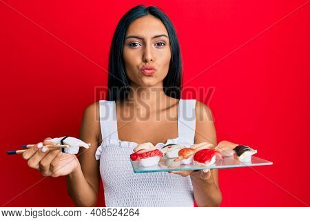 Young brunette woman eating butterfish sushi using chopsticks looking at the camera blowing a kiss being lovely and sexy. love expression.