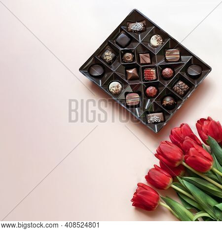 Box Of Chocolates And Red Tulips On Light Pink Background. Flat Lay, Top View.